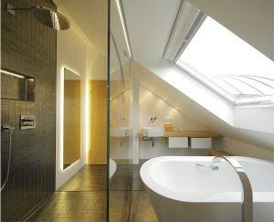 Die bodenebene Dusche dient in diesem kleinen Bad auch als Durchgang zu dem hinteren Bereich.